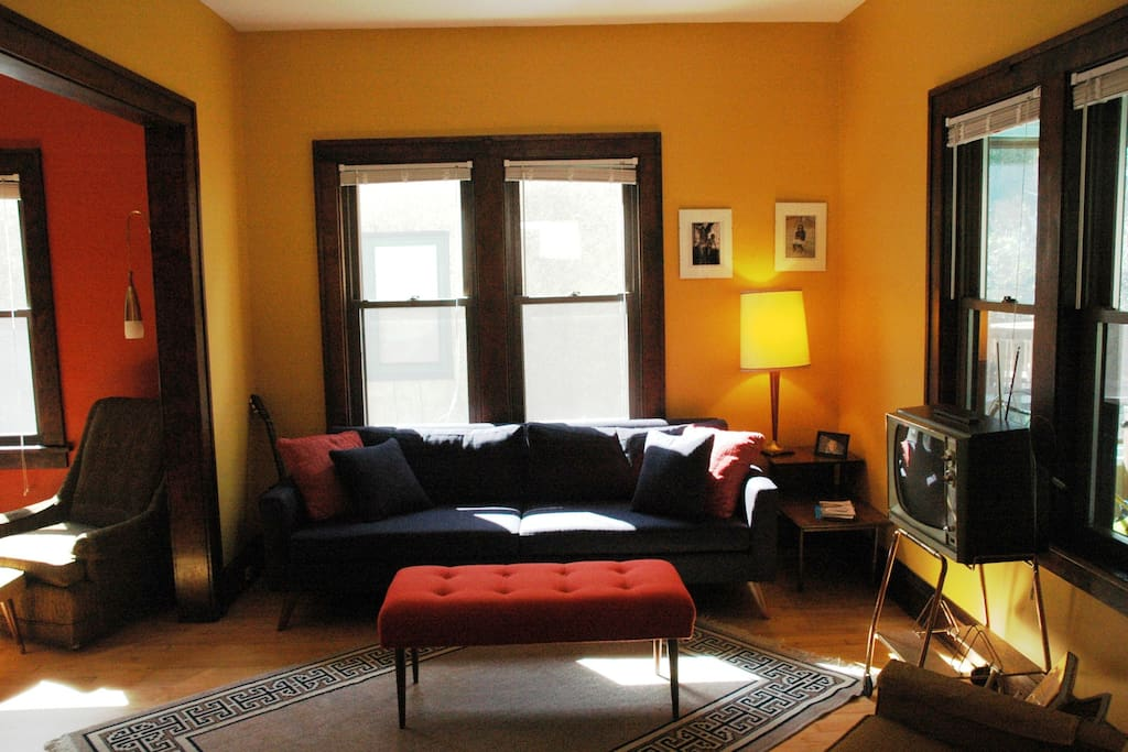 The living room is a mix of mod, antique, and new furnishings.