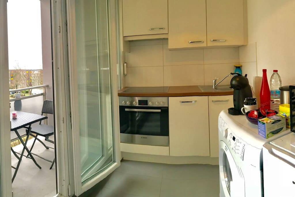 Kitchenette avec grandes baies vitrées balcon couvert