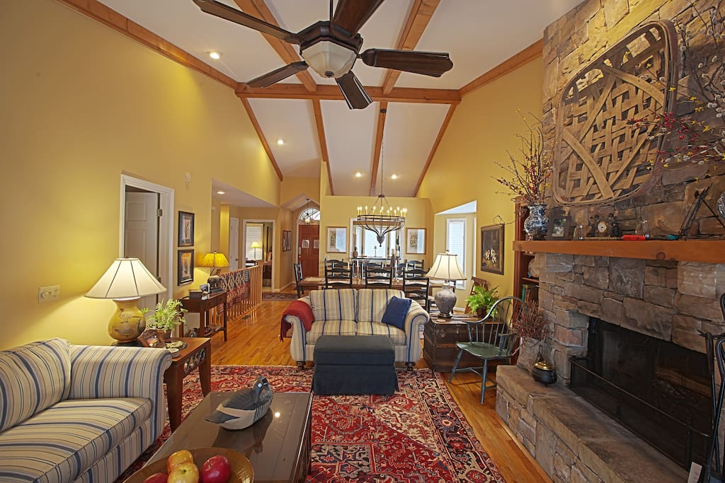 The great room of this Windsor town home offers hardwood floors, high vaulted ceilings with boxed beams, stone fireplace, and sliding glass doors that lead to an open deck. #fireplace