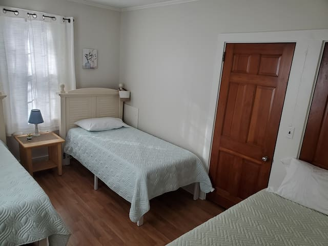 This bedroom has 3 twin beds and a closet.