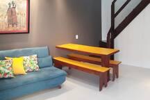 Sala de estar, com sofá cama, mesa, interfone, painel de TV + escada de acesso para os quartos