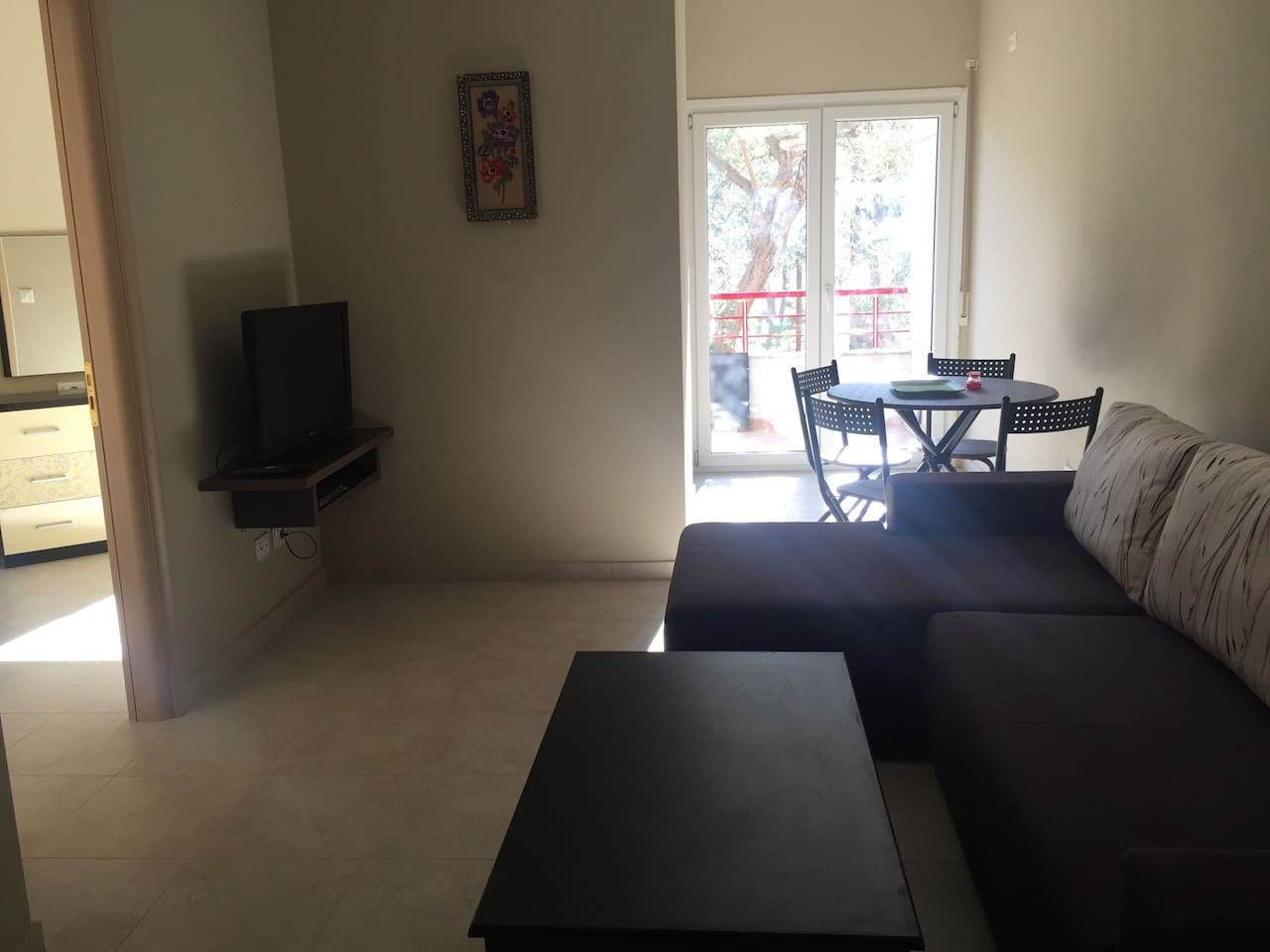 Living room with a large and comfortable sofa, dining table with chairs, a tv and a kitchen.