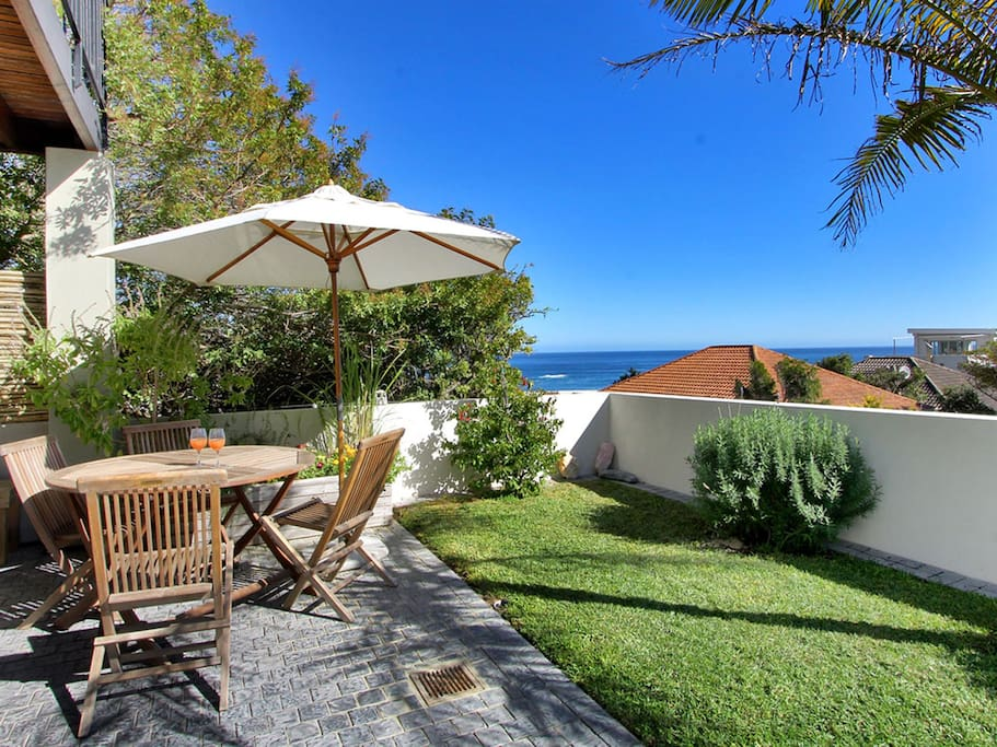 Small lawned garden with outdoor furniture and loungers