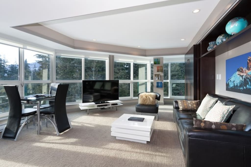 The spacious living area includes a TV, dining table and incredible mountain views.