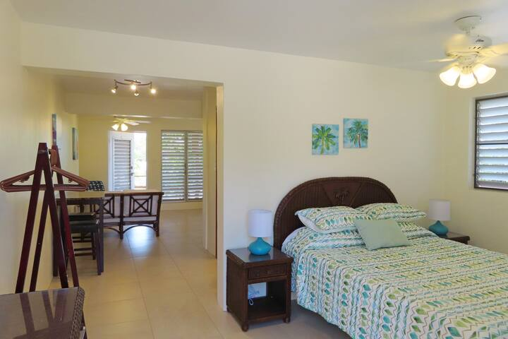 Bedroom with a memory foam queen sized  bed and screened louvered windows to enjoy the trade winds while you sleep.