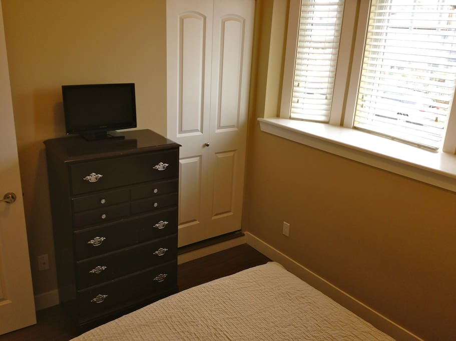 Closeup of dresser, closet and bay window area.