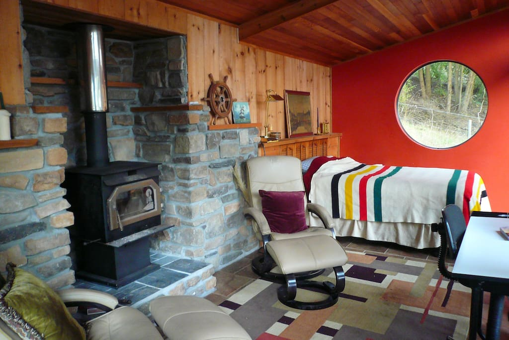 Guest cabin with double bed tucked into forested hillside