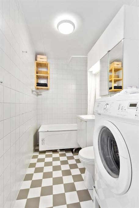 Bathroom with washer and bathtub with shower.