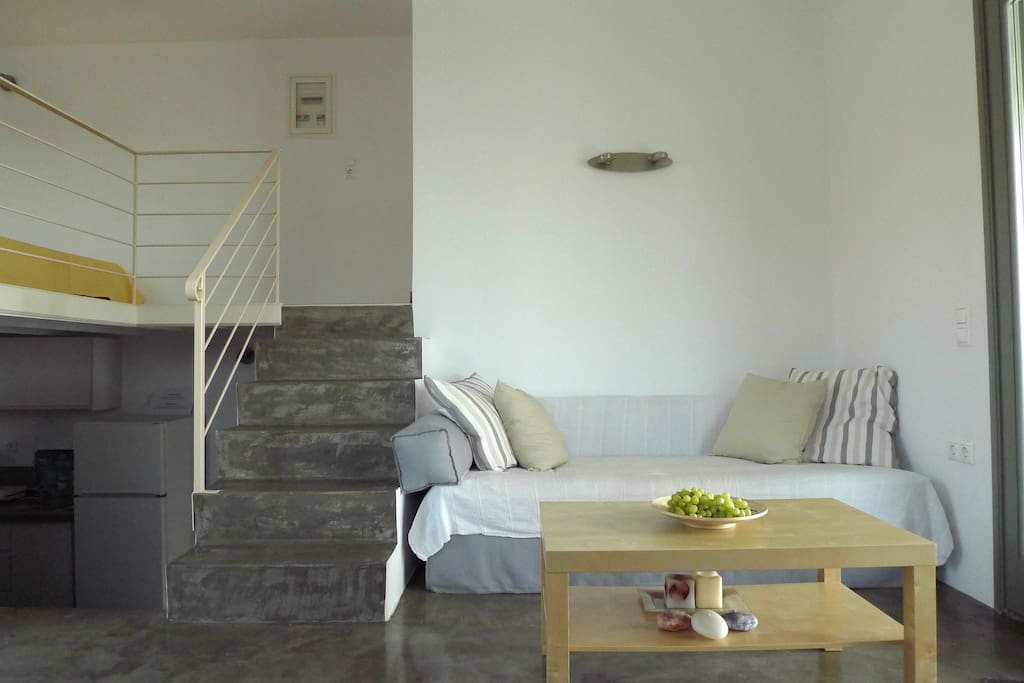The living room, sofa-bed and the stairs leading to the bedroom