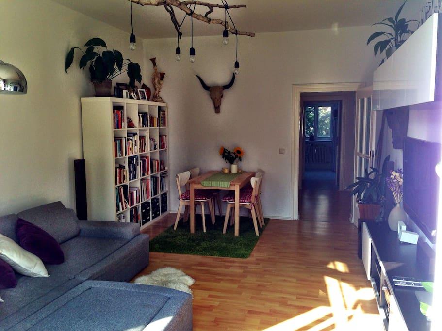 Wohnzimmer mit großer Buchauswahl und Essbereich