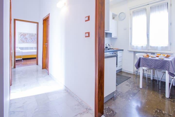 Cucina e corridoio che conduce ad una camera da letto e al bagno.