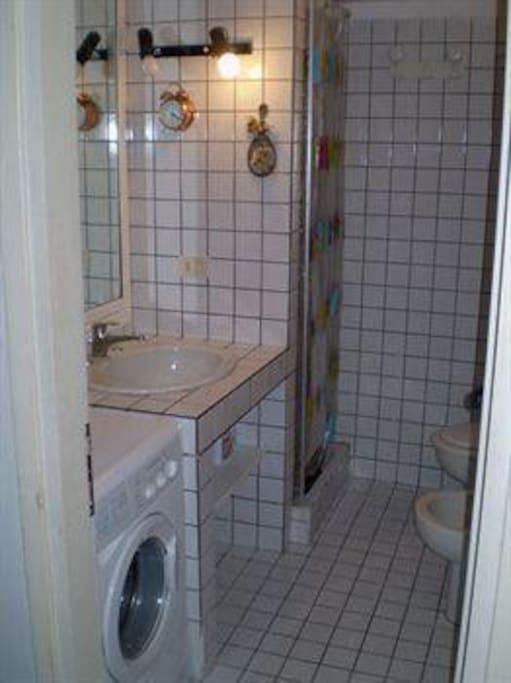 Bagno con piano doccia e lavatrice