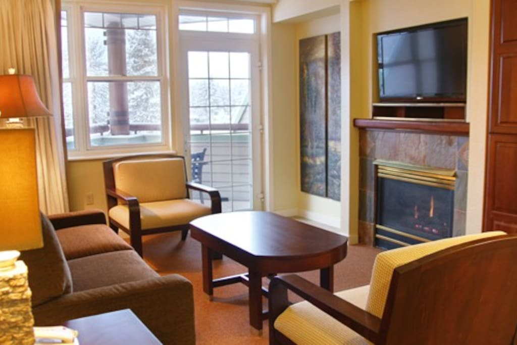 Living room with queen pull-out couch and gas fireplace, TV