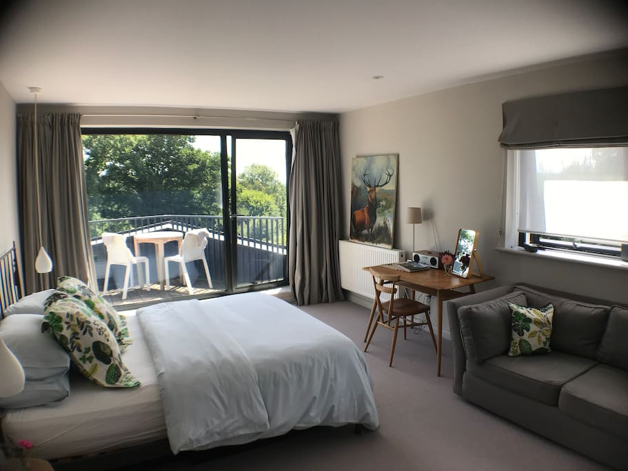 Spacious main bedroom with sofa, desk or dressing table, and own balcony