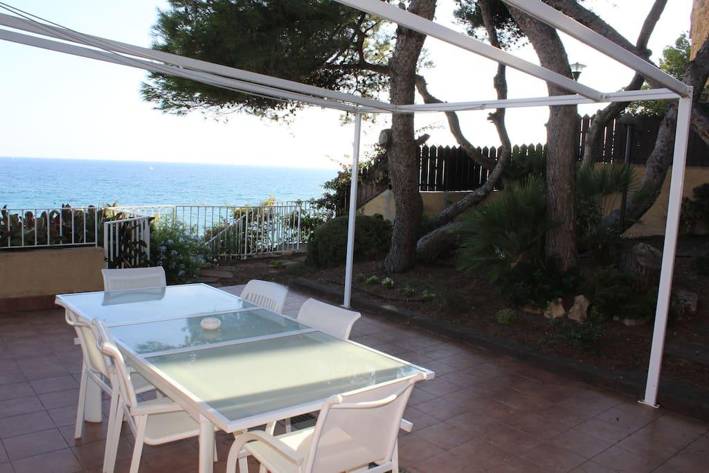 Terraza lateral con el mar de fondo, junto a un 70 m2 de jardín de pinos de formas espectaculares. Ideal para comer o cenar en verano.