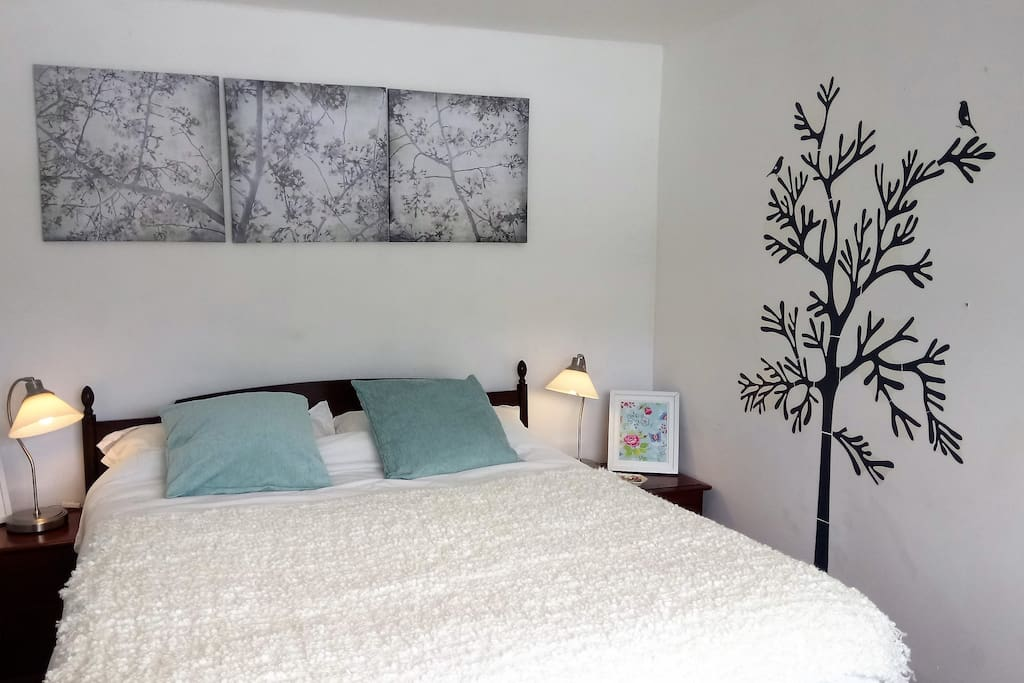 King size bed in double bedroom with neutral colours, wardrobe and bed side cabinets.