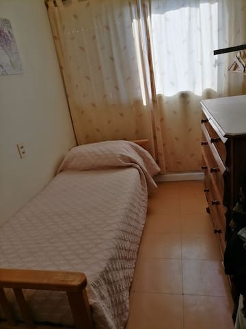 Cuarto individual con cama de una plaza y cómoda de cedro.