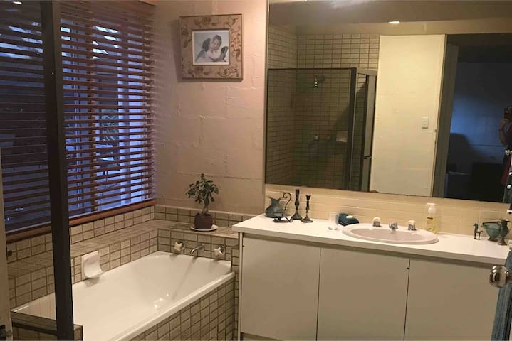 Guest bathroom with shower, bath, vanity, heater, mirrors, extra lighting, and ample space.  Separate toilet