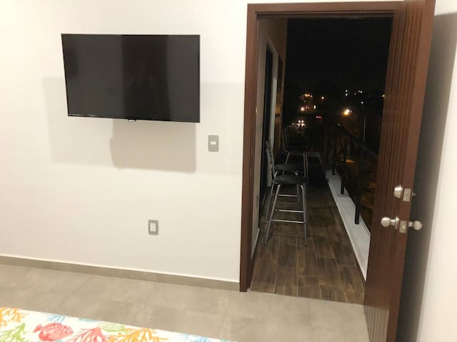 TV in bedroom with access to balcony