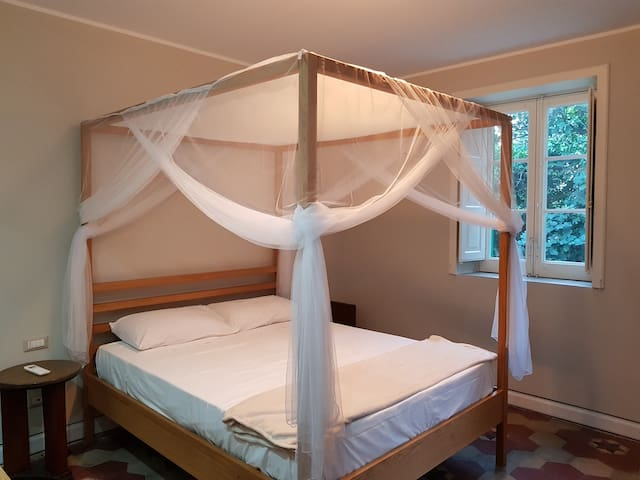 Il letto a baldacchino in legno naturale con la vista del giardino.