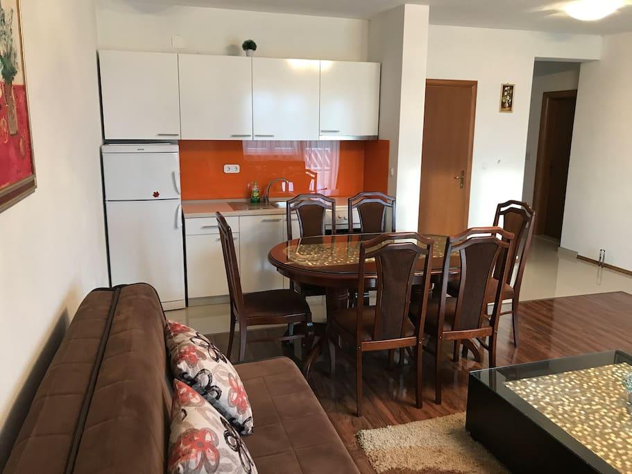 Ulazna vrata, kuhinja i sofa u dnevnom boravku