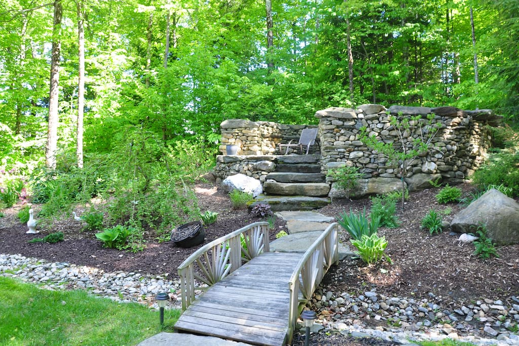 Quaint bridge crosses a stream to a large stone fire pit with built-in seating in the round