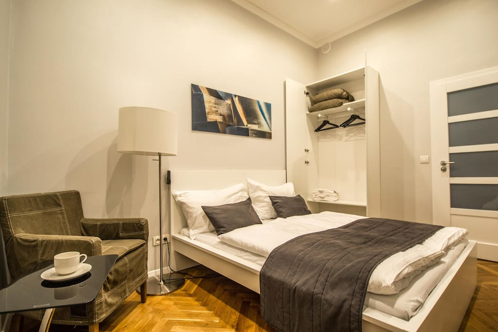 1st bedroom with big double bed, armchair and spacious wardrobe