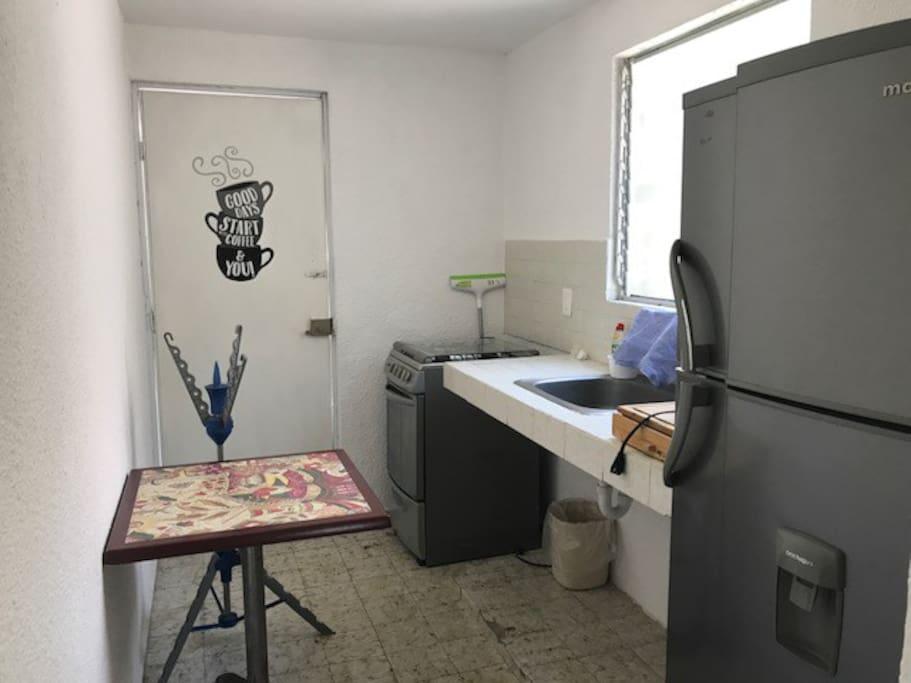 Pequeña cocina con todo lo necesario Estufa, horno,tostador Refrigerador,mesa desayuno,enseres. Patio de servicio