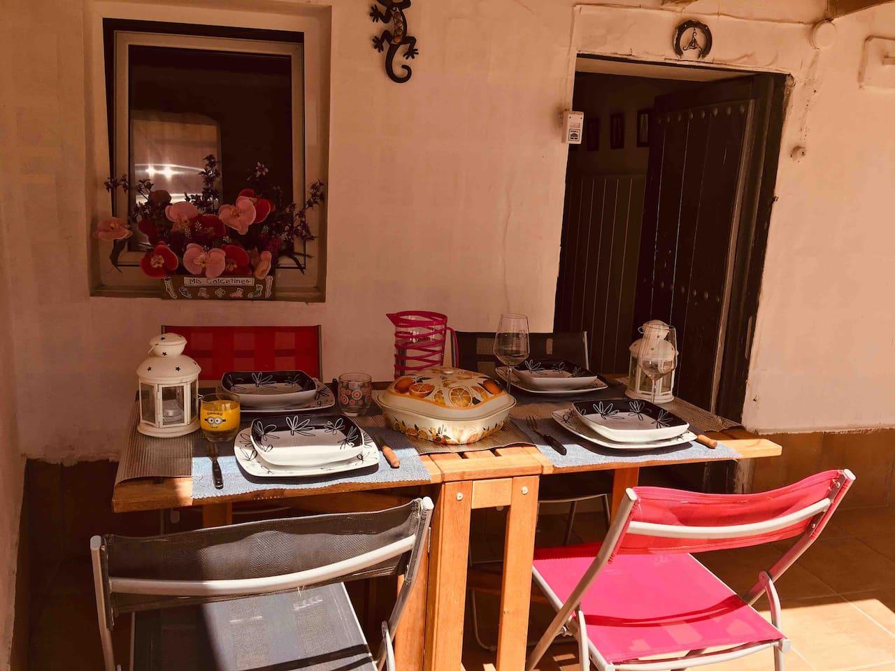 Zona del patio orientada al sur con mesa y sillas de exterior preparada para una perfecta comida al aire libre.