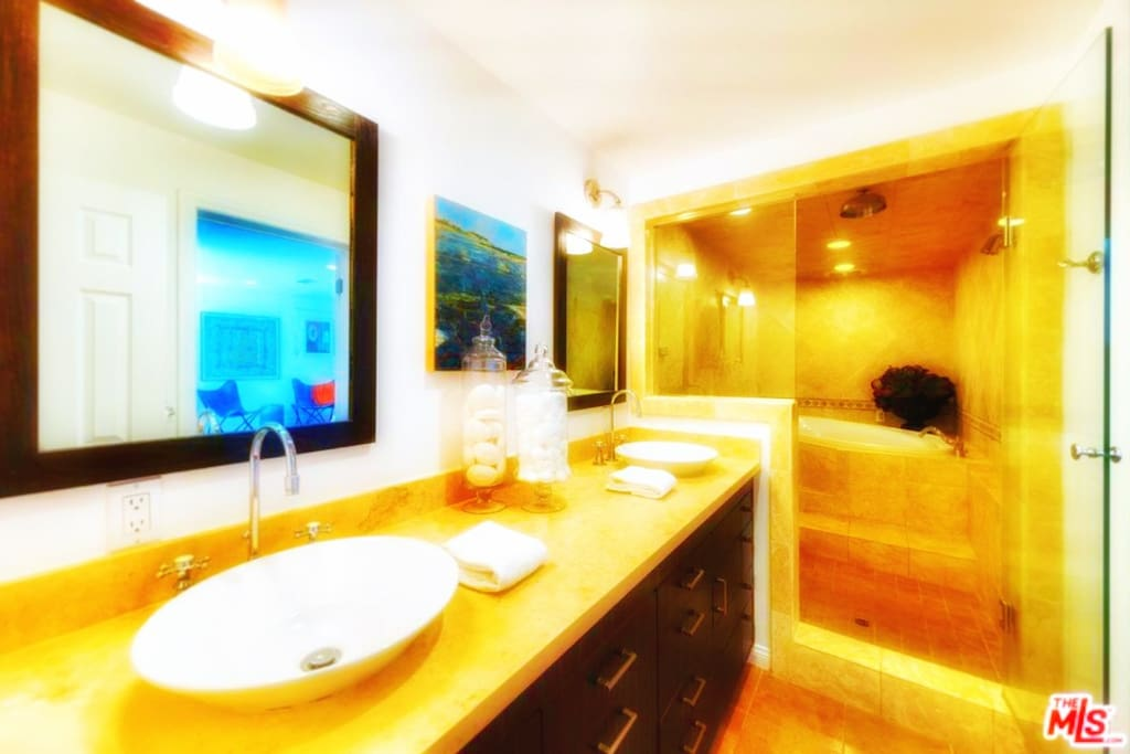 Your own PRIVATE EN-SUITE BATHROOM includes LARGE STEAM-ROOM, PRIVATE 2 PERSON JACUZZI TUB, TWO RAIN-DROP SHOWERS & TWO SINKS. PLUS: PLUSH HAND SOAP, LUXURIOUS SHAMPOO, CONDITIONER, AND BUBBLE BATH, BATH TOWELS & HAND TOWELS.