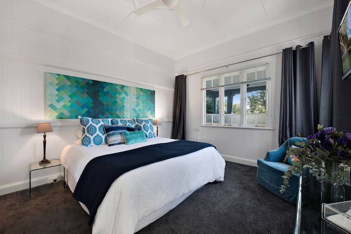 Stylish master bedroom with king sized bed and personal TV