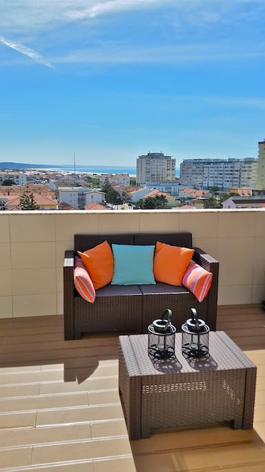Lounge area of the sunny terrace with panoramic view over Costa da Caparica rooftops and ocean