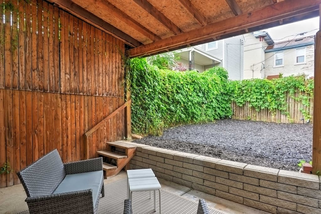 The covered patio area is complete with wicker furnishings.