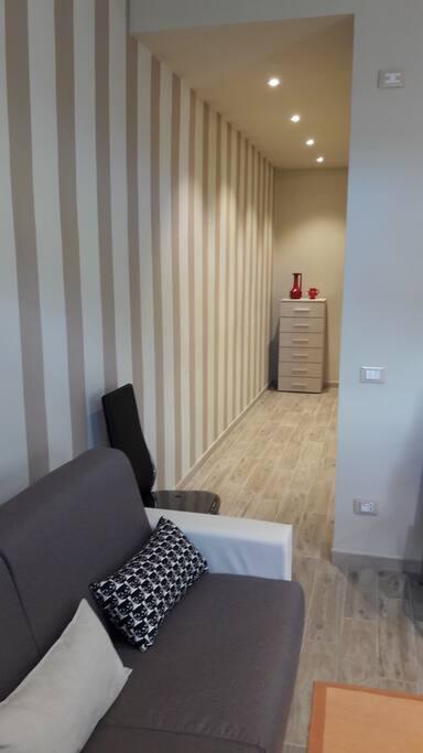 Divano letto nella sala comune e corridoio che porta alle camere