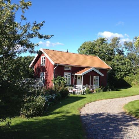 Röd stuga på landet - en idyll i vackra Dalsland