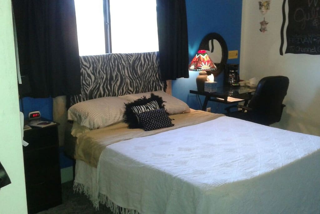 Zebra room has desk and bedside table, alarm clock, stained glass lamp and coffee station.