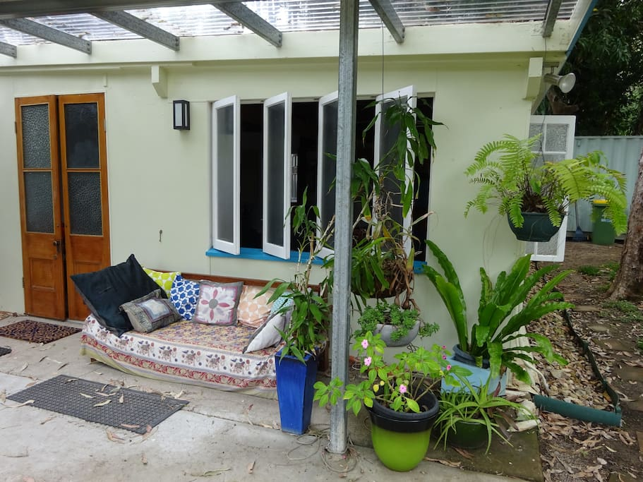 Part of front verandah of beach bungalow with day bed and tropical plants