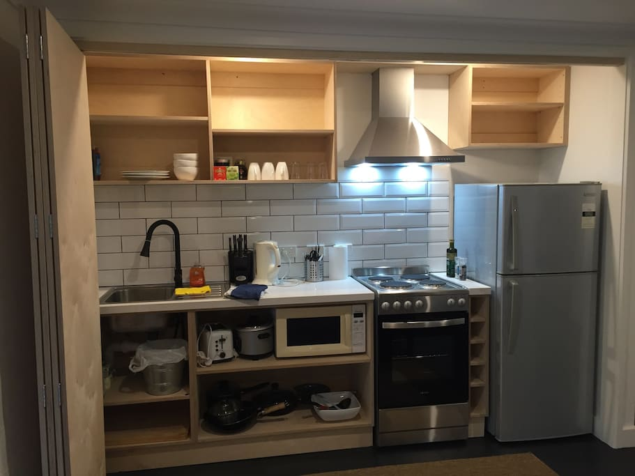 Full kitchenette with cooking utensils, cutlery and chinaware