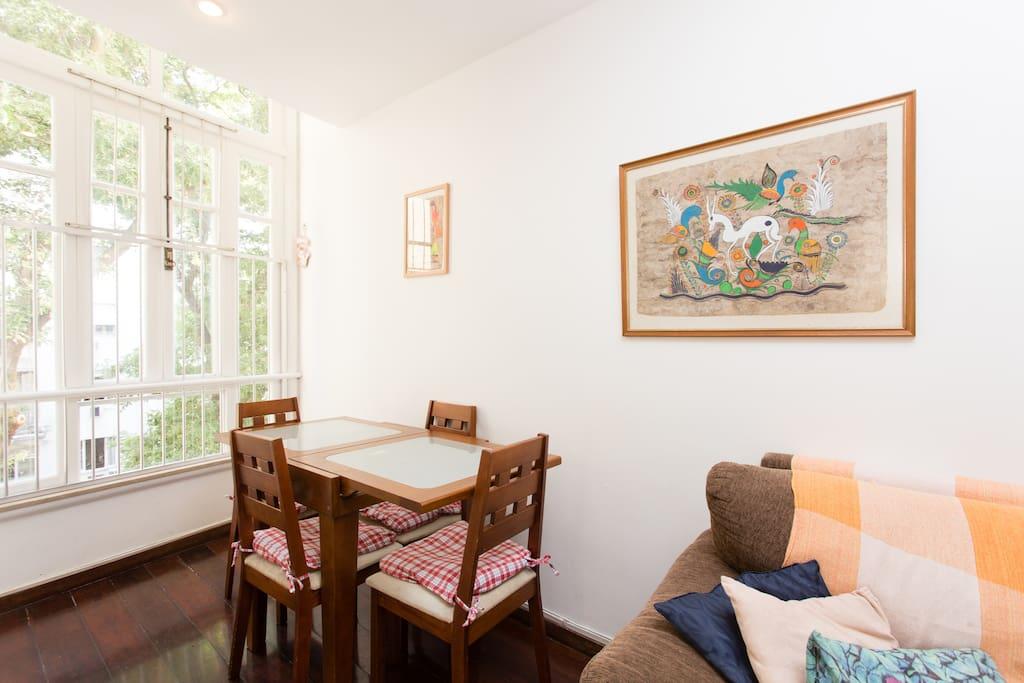 Sala com mesa e vista arborizada.