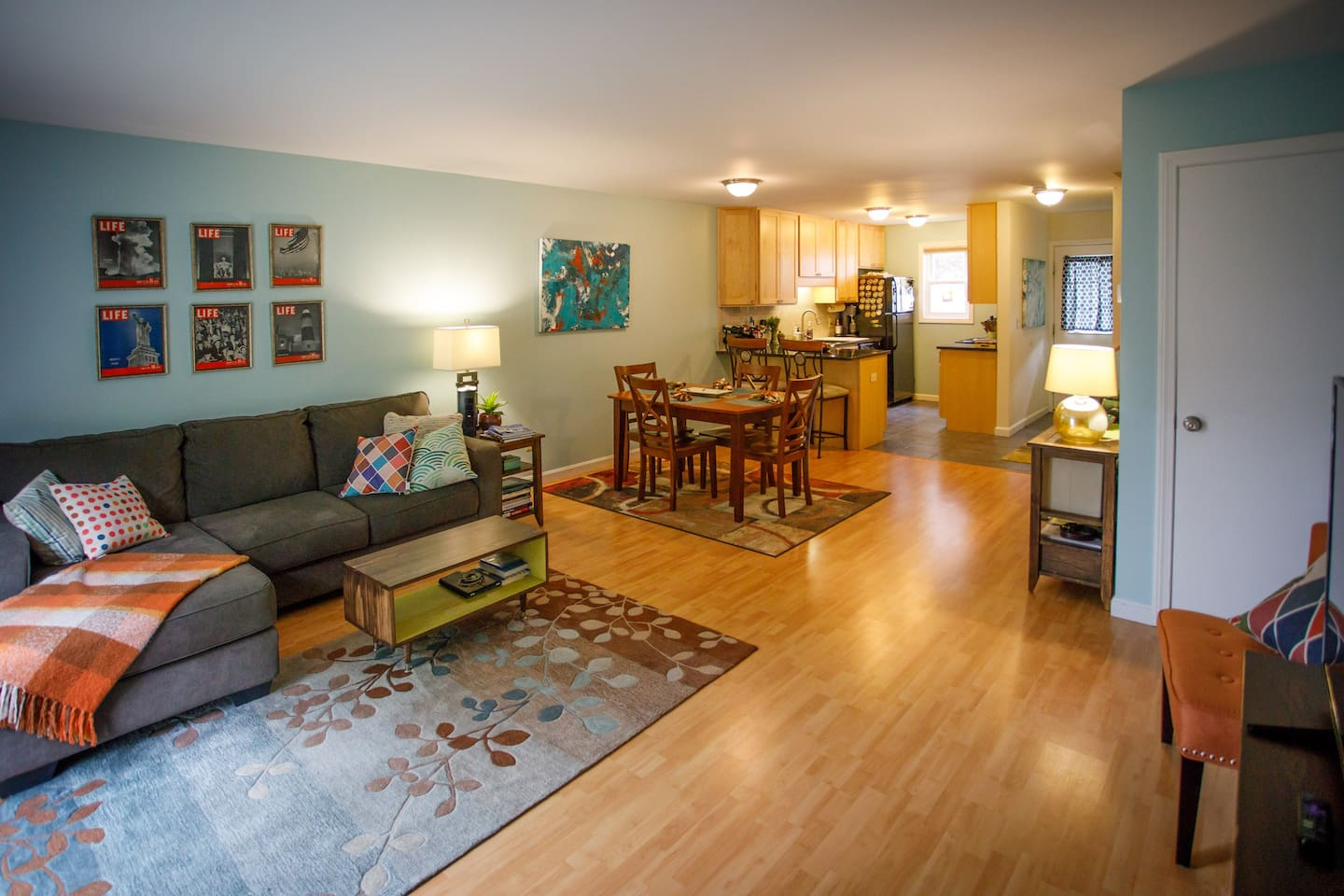 """Downstairs with an open floor plan with living room, large 45"""" TV,  dining table, kitchen, 1/2 bath and sliding glass doors to back porch."""