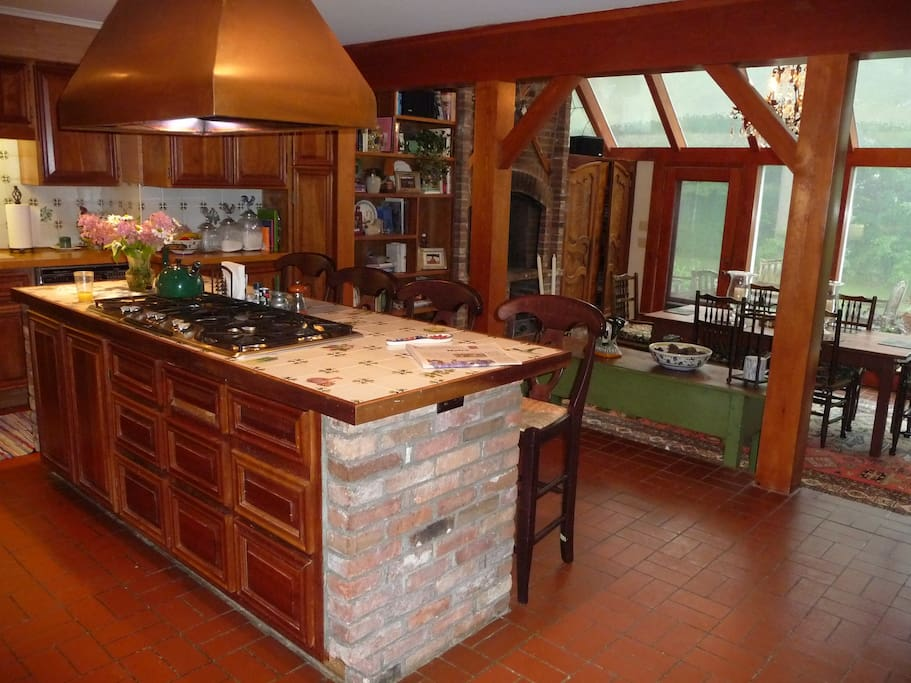 Fully equipped country eat in kitchen with fireplace by the dining area