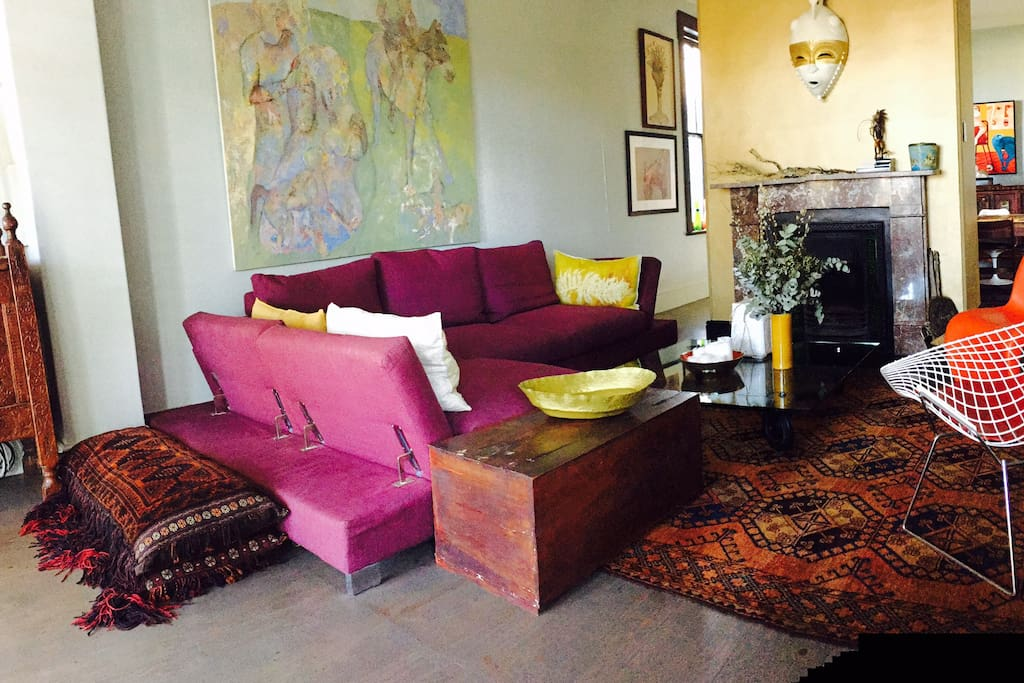 Spacious and comfortable down filled sofa with eclectic art and antic furniture