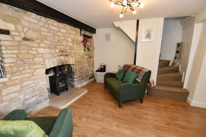 Cosy lounge with woodburner, and stairs to the landing room and bedroom