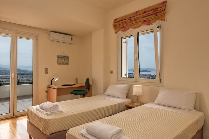 Fourth room with two sigle beds. The two singles beds can be united.There is a balcony with view to sea, mountains and city of Chania. Bedroom with aircondition.