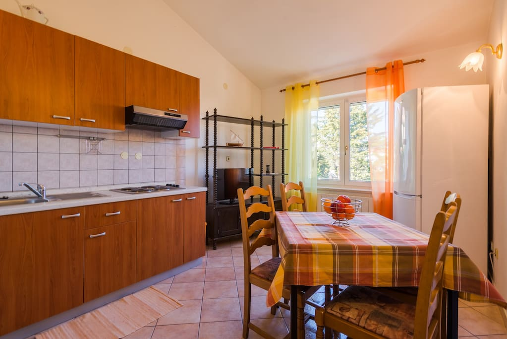 Day area with kitchen, dining table, couch and flat TV.