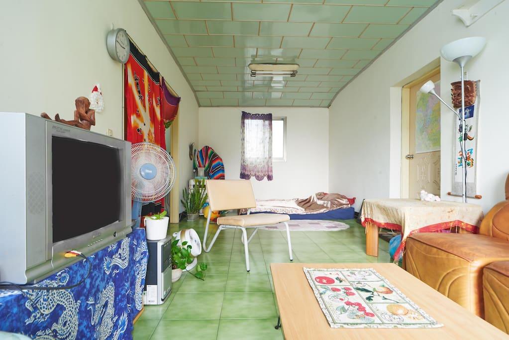 開放式客廳和床.有布簾隔開.