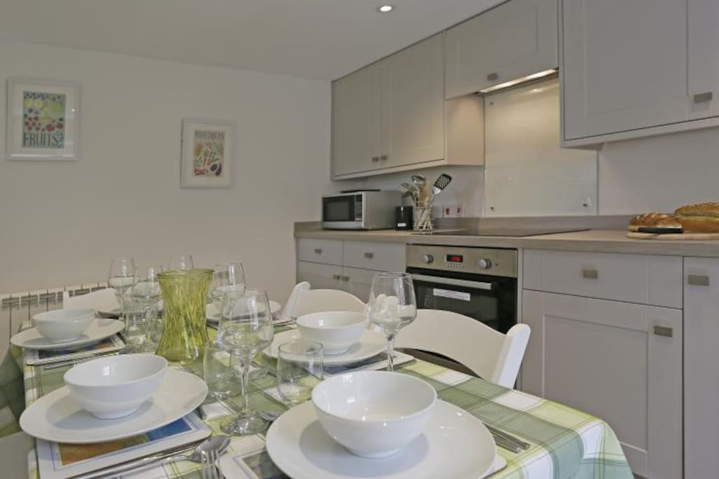 Open Plan Room with Kitchen/Dining Area: Electric oven and ceramic hob, fridge, slimline dishwasher, dining table and chairs. Tea and Coffee starter pack supplied. Utility Room Seperate