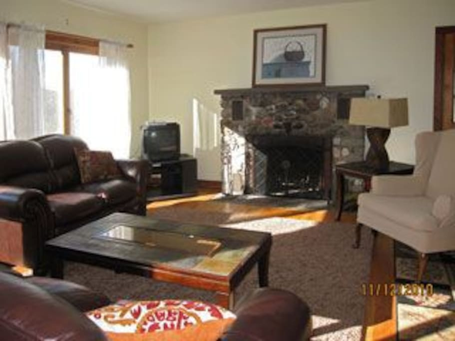 Fieldstone fireplace in sun-filled living room for a cozy fire after leap peeping.