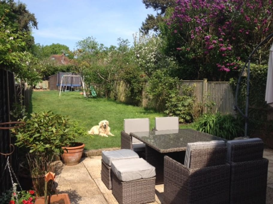 Garden (patio, dining set, deck at far end, trampoline, swings)