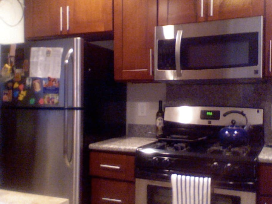 renovated shared kitchen with stove, refrigerator, microwave, dishwasher